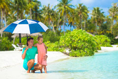 Father and little girl with umbrella hiding from Royalty Free Stock Photos