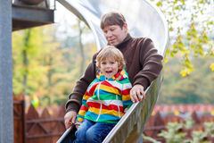 Father and little kid boy sliding on playground Royalty Free Stock Image
