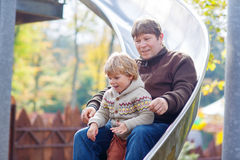 Father and little kid boy sliding on playground Stock Images