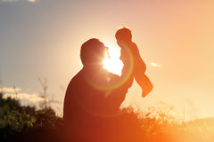 Father and little newborn daughter silhouettes at sunset Royalty Free Stock Photography