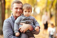 Father with little son is in autumn city park. Bright yellow trees. royalty free stock images