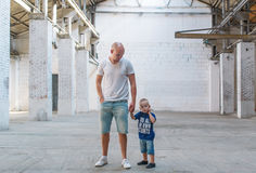 The father and the little son in the big abandoned factory shop Royalty Free Stock Images