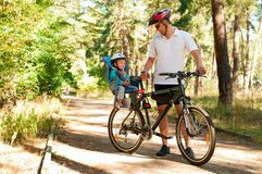 Father and little son on bike royalty free stock photography