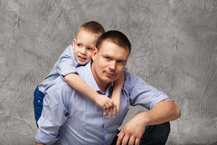 Father and little son in blue shirts in front of gray background Stock Images