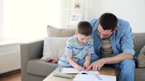 Father and little son with crayons drawing at home stock footage