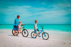 Father with little son and daughter biking on beach royalty free stock images