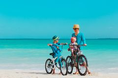 Father with little son and daughter biking on beach. Vacation stock photos