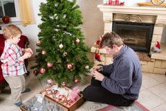 Father and little son decorating christmas tree at home Royalty Free Stock Image