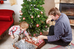 Father and little son decorating christmas tree at home Stock Images