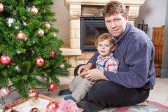 Father and little son decorating christmas tree at home Stock Photo