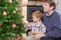 Father and little son decorating christmas tree at home. Little preschool boy and his father decorating christmas tree at home with chimney royalty free stock images