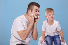 A father and little son have fun , dad smears his face with shaving foam. On a blue background. royalty free stock photography