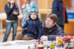 Father and  little son having fun on toy exposition, indoors. Royalty Free Stock Images