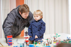 Father and  little son having fun on toy exposition, indoors. Royalty Free Stock Photos