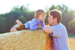 Father and little son having fun on yellow hay field in summer Royalty Free Stock Photos