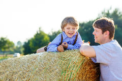 Father and little son having fun on yellow hay field in summer Stock Photos