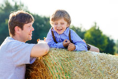 Father and little son having fun on yellow hay field in summer Royalty Free Stock Photography