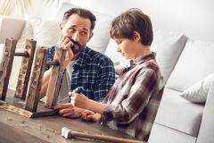 Father and little son at home dad holding nail looking curious at boy holding screwdriver stock images