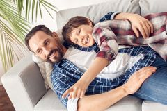 Father and little son at home lying on sofa hugging watching tv together joyful stock photography