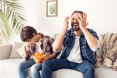 Father and little son at home sitting on sofa boy holding potato chip covering face disappointed while father shouting stock image