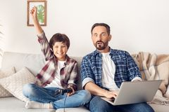 Father and little son at home sitting on sofa dad using laptop looking at tv shocked while boy holding controller hand royalty free stock images