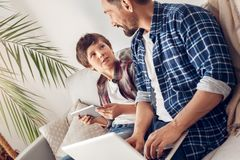 Father and little son at home sitting on sofa dad working on laptop while boy using digital tablet discussing pastime royalty free stock photo
