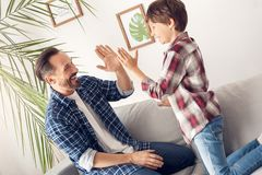 Father and little son at home sitting on sofa giving high five looking at each other happy royalty free stock image
