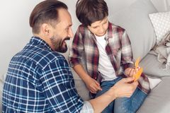 Father and little son at home sitting on sofa playing forehead detective looking at stickers laughing royalty free stock photos