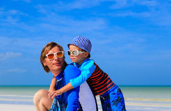 Father and little son hug on summer beach Stock Photography