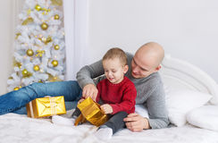 Father and little son lie on bed. They unpack Christmas gifts. The father and the little son lie on a bed and unpack Christmas gifts. The father gives his son a Royalty Free Stock Images