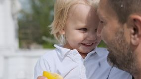 Father and little son look at each other with love. A man holds a child in his arms. close-up. Brutal Father and little son in white clothes look at each other stock footage