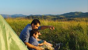 Father And Little Son Looking Away Sitting At The Tourist Tent In The Mountains stock footage