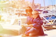 Father and little son looking at map in harbor Royalty Free Stock Photo
