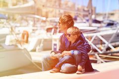 Father and little son looking at map in harbor Stock Photography
