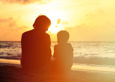 Father and little son looking at sunset on beach. Silhouette of father and little son looking at sunset on beach Stock Photo