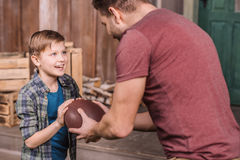 Father with little son playing american football with ball at backyard. Dad and son playing Royalty Free Stock Photography
