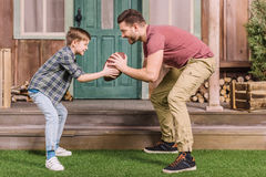 Father with little son playing american football with ball at backyard. Dad and son playing royalty free stock images