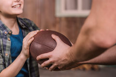 Father with little son playing american football with ball at backyard. Dad and son playing royalty free stock photos