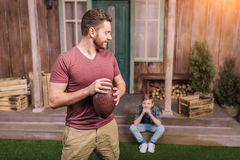 Father with little son playing american football with ball at backyard. Dad and son playing stock images
