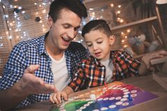 Father and little son are playing board game at night at home. Father and little son are playing board game at table at night at home royalty free stock image