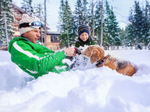 Father and little son playing with their beagle in deep snow Stock Photo