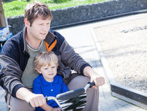Father and little son playing together outdoors on toy car Royalty Free Stock Image