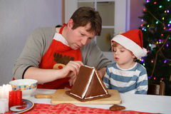 Father and little son preparing a gingerbread cookie house Stock Photography