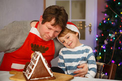 Father and little son preparing a gingerbread cookie house Stock Photo