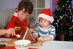 Father and little son preparing a gingerbread cookie house Royalty Free Stock Photo