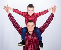 Father little son red shirts family look outfit. Child riding on dads shoulders. Happiness being father of boy. Having. Fun. Fathers day. Father example of royalty free stock photos