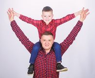 Father little son red shirts family look outfit. Child riding on dads shoulders. Happiness being father of boy. Having. Fun. Fathers day. Father example of stock photo