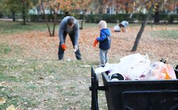 Father and little son scavenging in the park. Background - trash and litter bin. The concept of ecology and protecting the planet. The concept of ecology and royalty free stock image