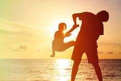 Father and little son silhouettes play at sunset Royalty Free Stock Photos