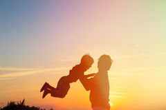 Father and little son silhouettes play at sunset Royalty Free Stock Images
